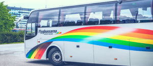 Gray bus with rainbow print on the side. Photo.